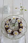 Kranz mit Anemonen in geschliffener Glasschale mit Glasglocke