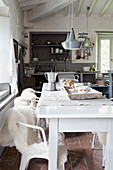 Chairs with fur blankets at white dining table in front of rustic open-plan kitchen