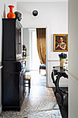 Black cabinet on mosaic-tiled floor in classic interior