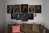 Antique portraits hung along horizontal axis above sofa