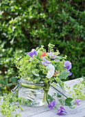 Bouquet of sweet peas and lady's mantle in a mason jar