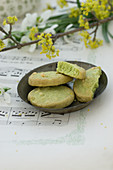 Bowl of pistachio biscuits on sheet music