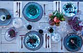 Weihnachtlich gedeckter Tisch mit blau-weiß gespreckeltem Geschirr und Lichterkette