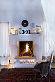 Seating area in front of festively decorated open fireplace in country house