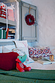 Festively decorated shelves in niche cupboard with doors above bed