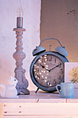 Vintage alarm clock, candlestick with light bulb and animal figurine on wooden bench