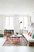 Sofa aus Paletten im Wohnzimmer mit weißem Boden und Farbakzenten