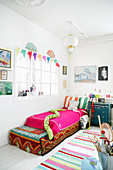 Child's bedroom with interior window decorated in white with brightly coloured accents