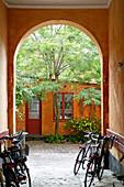 Fahrräder in der Hausdurchfahrt mit Bogen zum sommerlichen Innenhof