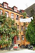 Wäscheleine und Rosenranken am gelben Altbau mit Innenhof