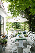 Dining table and parasol on summery terrace outside house