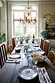 Set table and chandelier in country-house-style dining room
