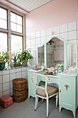 Antique, turquoise dressing table in bathroom with pink walls