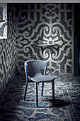 Black Mahogany chair with woven seat and back in interior with mosaic-tiled walls and floor