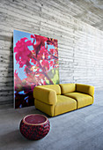 Red pouffe and mustard-yellow outdoor sofa in front of large floral photograph