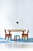Spherical designer lamp above wooden table with wooden chairs and stool