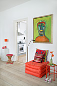 Orange pouffe below green painting in living room