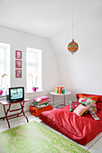 Large red beanbag in living room with colourful accents