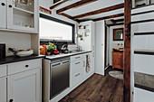White kitchen counter below mezzanine in tiny house