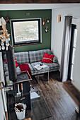 Kariertes Sofa vor grüner Wand und Ofen im Tiny House