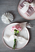 Pastel arrangement: pink carnations tied with ribbon on plate