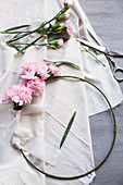 Pink carnations tied to metal ring with ribbon
