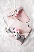 Deko in Pastell: Umschläge mit Stoffschleifen und Nelken in Rosa