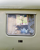 View through window into old caravan with vintage-style accessories