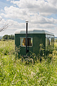 Vintage-style green caravan with chimney in summery meadow