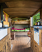 Bunk beds and kitchen in rustic tiny house with wooden floor