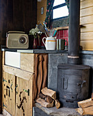 Wood-burning stove next to sink in rustic tiny house