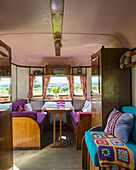 Wooden furnishings and colourful upholstery in old caravan