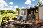 Rustikale Terrasse mit Couchtisch und Liegestühlen am Tiny Home