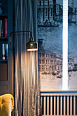 Lamp mounted on shelves next to window with curtains and shutters