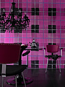 Tulip table and black chandelier in front of wall with wallpaper in oversized pink-and-black tartan pattern