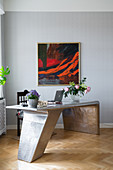 Flowers on modern metal desk below abstract painting on wall