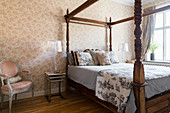 Four-poster bed with turned wooden posts in classic bedroom