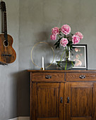 Candlestick and peonies on old cabinet next to guitar hung on grey wall