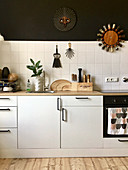 Decorations on black wall above tiled splashback in kitchen