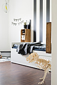 Wooden dinosaur skeleton in child's bedroom with wide stripes on wall