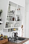 Crockery and glasses on slanted kitchen shelves above sink