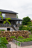 Raised beds and stacked firewood in garden of wooden house
