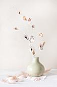 Mit Muscheln beklebte, weiß bemalte Zweige in einer Vase