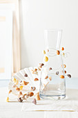 Delicate garland of wire and small seashells wound around carafe