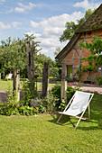 Deckchair in summer garden with thatched house in background