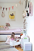 Girl playing in pretty, pink-and-white bedroom