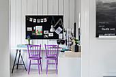 Purple spoke-back chairs and desk below pinboard on wall