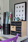 Small chest of drawers with chalkboard fronts and poster of animal tracks