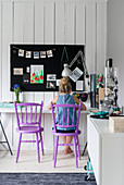 Girl sitting on purple chair at desk below black pinboard on wall