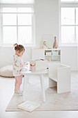 Little girl at play table in child's bedroom decorated entirely in white
